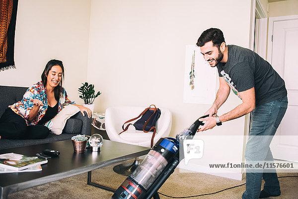 Frau überwacht den Mann beim Staubsaugen des Teppichs