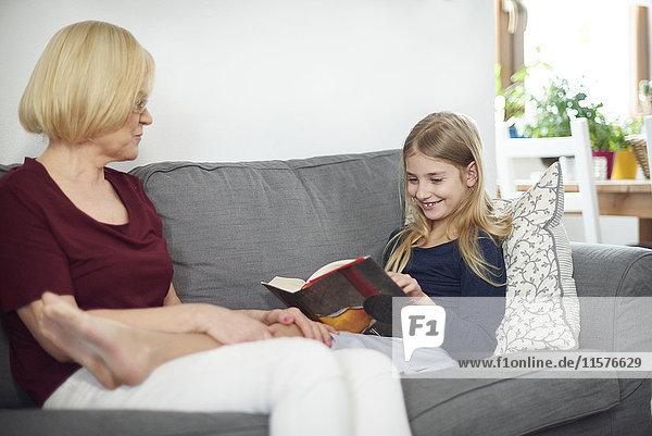 Großmutter und Enkelin lesen Buch auf Sofa