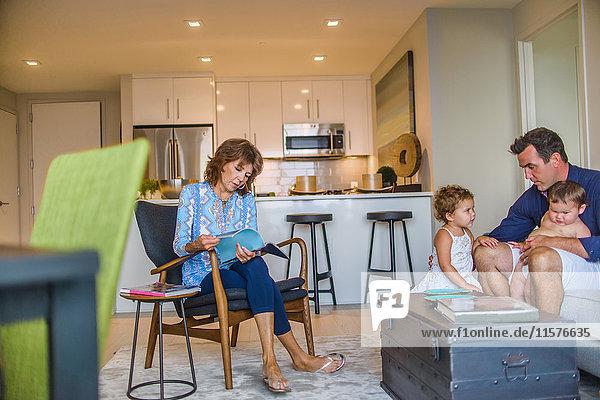 Vater und zwei kleine Kinder auf dem Sofa sitzend  Großmutter auf einem Stuhl sitzend  Zeitschrift durchblätternd