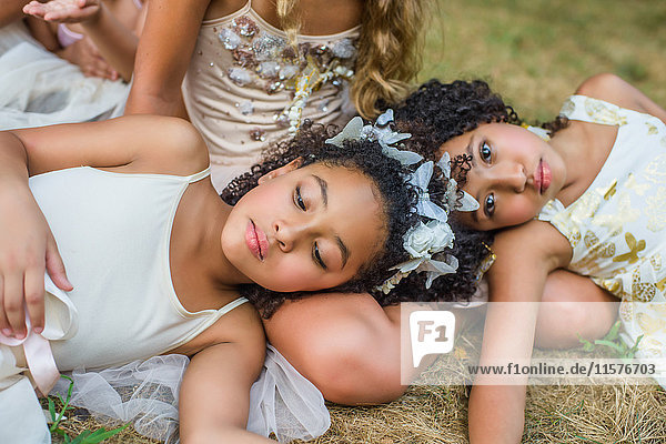 Group of young girls  dressed as fairies  lying on grass