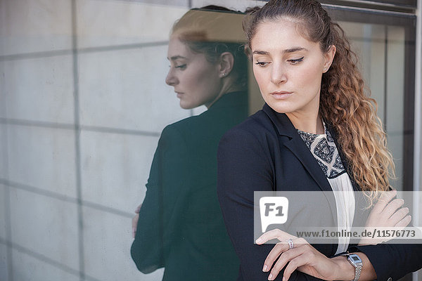 Porträt einer jungen Geschäftsfrau  Arme verschränkt  an Fenster gelehnt