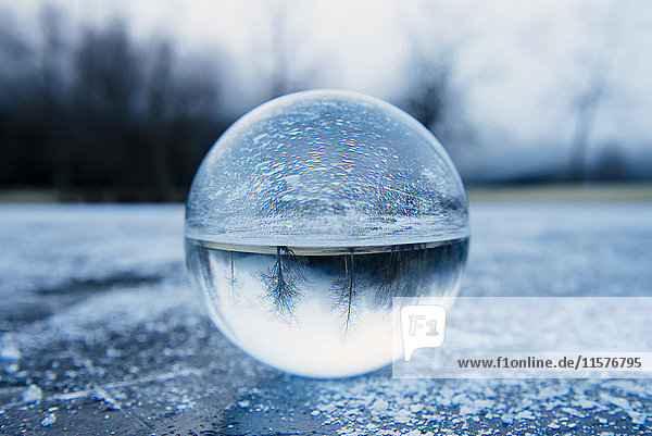 Close up of crystal ball on frozen lake