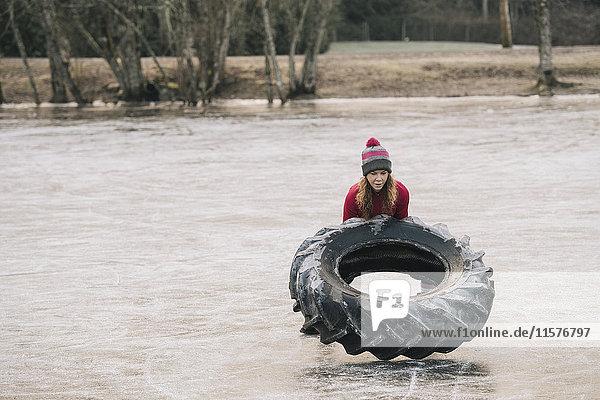Woman flipping tyre on frozen lake