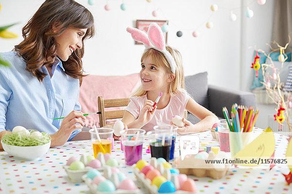 Mädchen und Mutter bemalen Ostereier bei Tisch