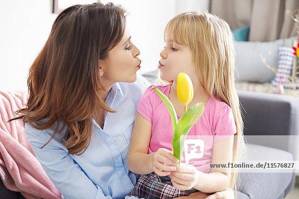 Mädchen  das der Mutter eine Tulpe reicht und auf dem Sofa die Lippen kräuselt