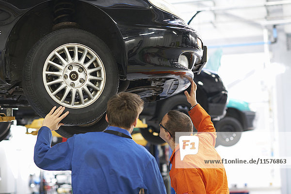 Rear view of college mechanic students inspecting underneath of car
