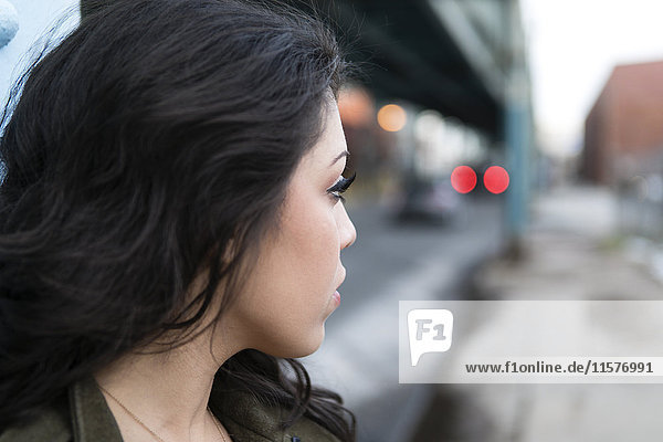 Profile portrait of young woman in city looking over her shoulder