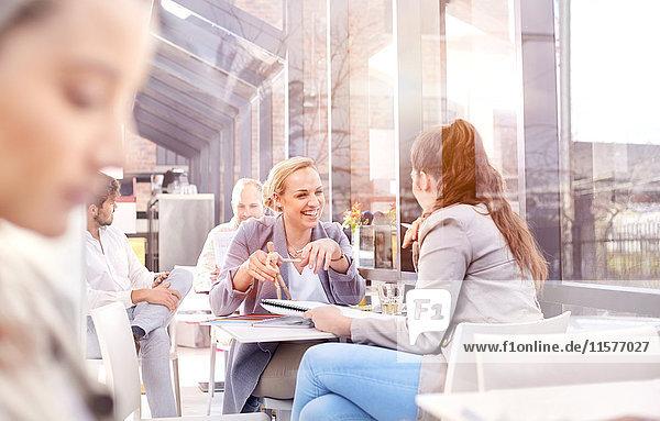 Businesswomen having discussion during working lunch in restaurant