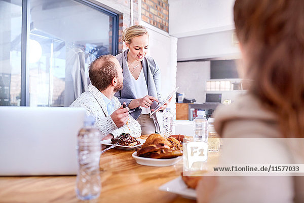 Businesswoman and man using digital tablet during working lunch in restaurant