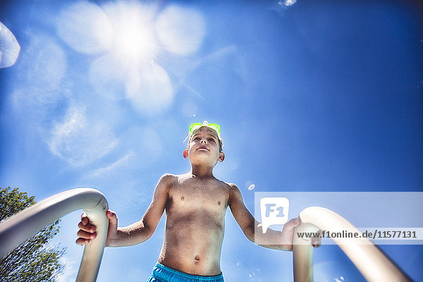 Low angle view of boy on swimming pool ladder against blue sky