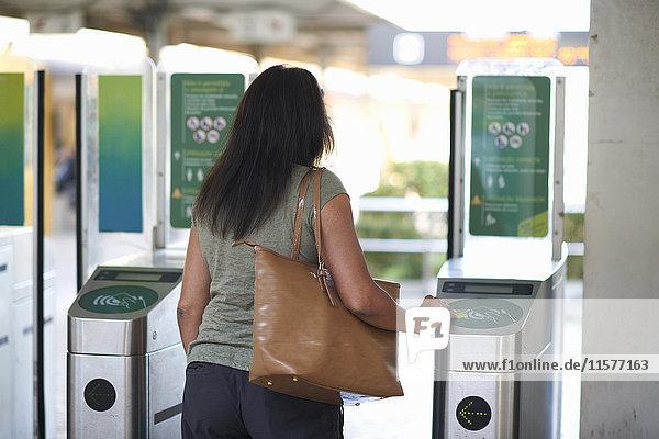 Rückansicht einer Frau  die den Touchscreen der Fahrkarte an der Bahnschranke benutzt