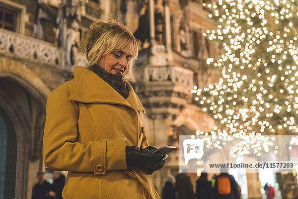 Frau betrachtet Smartphone bei nächtlicher Weihnachtsbaumbeleuchtung  München  Deutschland