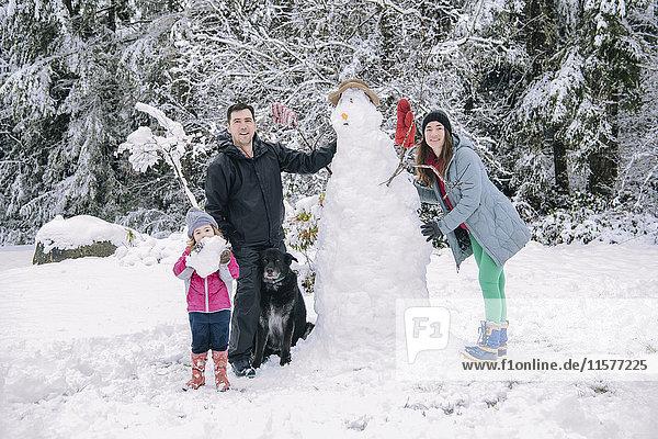 Porträt einer jungen Familie  die einen Schneemann baut