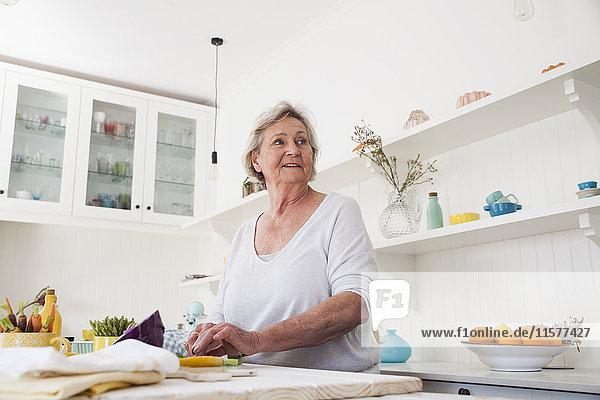 Ältere Frau  die beim Zubereiten von Gemüse am Küchentisch über ihre Schulter schaut