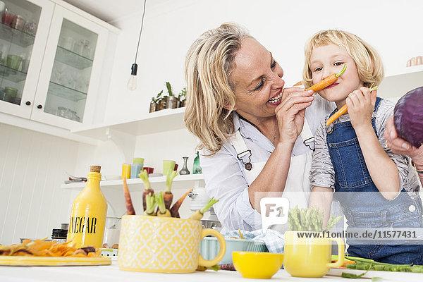 Reife Frau macht der Tochter am Küchentisch einen Karottenschnurrbart