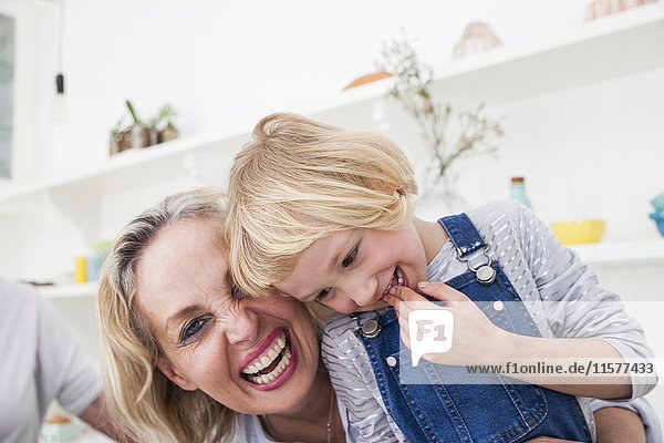 Portrait of girl and mother laughing in kitchen