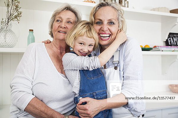 Portrait of girl hugging mother and grandmother in kitchen