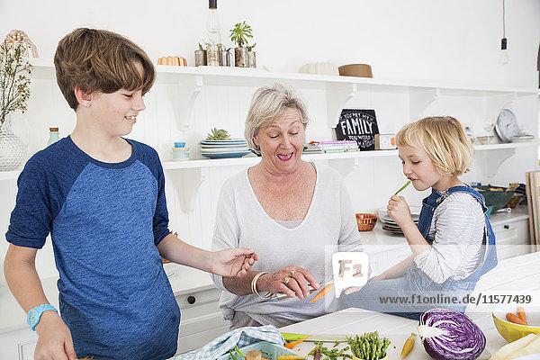 Ältere Frau und Enkelkinder bereiten Gemüse am Küchentisch