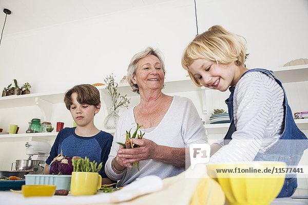 Ältere Frau bereitet frisches Gemüse am Küchentisch mit den Enkelkindern