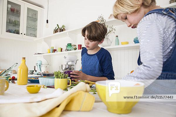 Mädchen und Bruder bereiten frisches Gemüse am Küchentisch zu