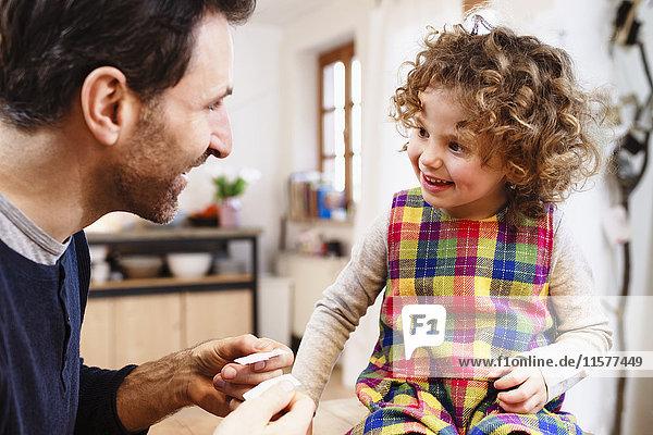 Reifer Mann zeigt Tochter Klebepflaster in der Küche