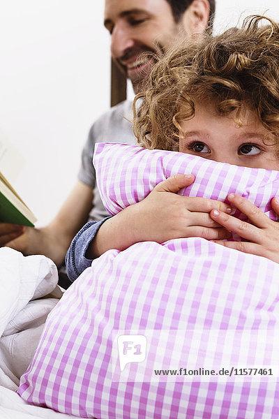 Mädchen umarmt Kissen  während der Vater im Bett ein Märchenbuch liest
