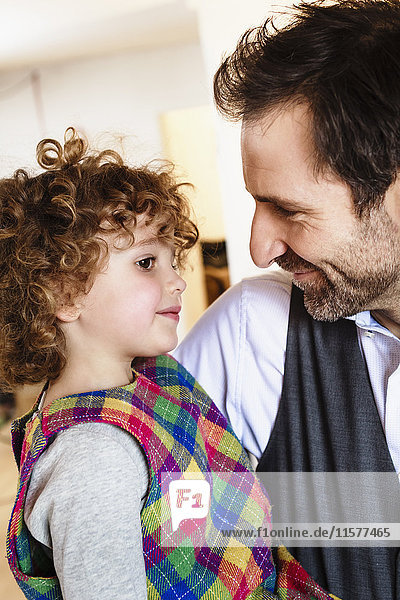 Loving man carrying daughter in arms