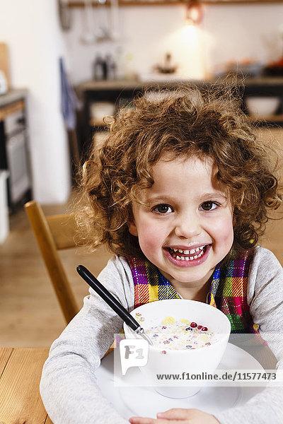 Porträt eines Mädchens mit zahnigen Grinsen  das Getreide in der Küche hat