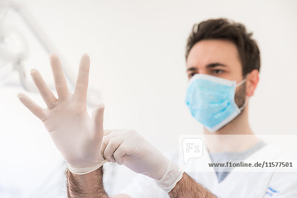 Männlicher Zahnarzt zieht Nitril-Handschuhe an