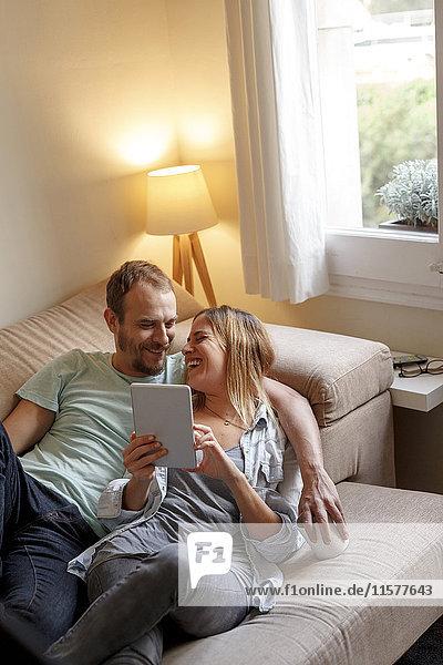 Mittelgroßes erwachsenes Paar entspannt sich auf dem Sofa und schaut auf ein digitales Tablett