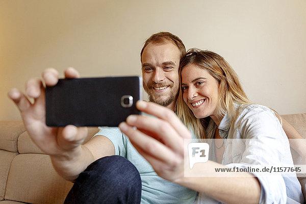 Mittelgroßes erwachsenes Paar  das sich auf dem Sofa entspannt  Selfie nimmt  ein Smartphone benutzt