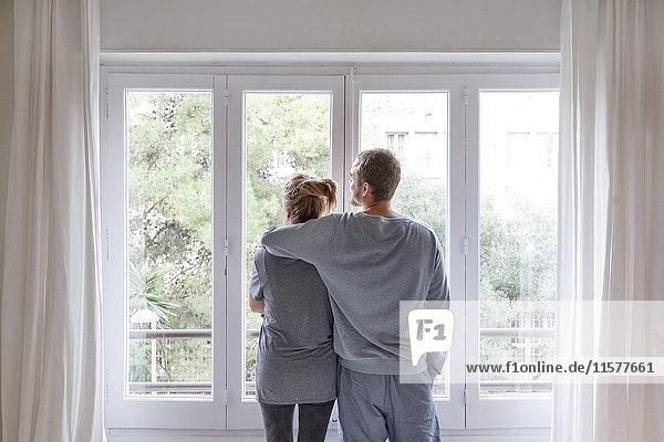 Mittleres erwachsenes Paar zu Hause  Blick aus dem Fenster  Mann umarmt Frau  Rückansicht