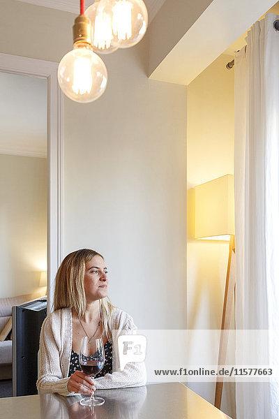 Frau zu Hause  die am Tisch sitzt  ein Glas Wein hält und aus dem Fenster schaut