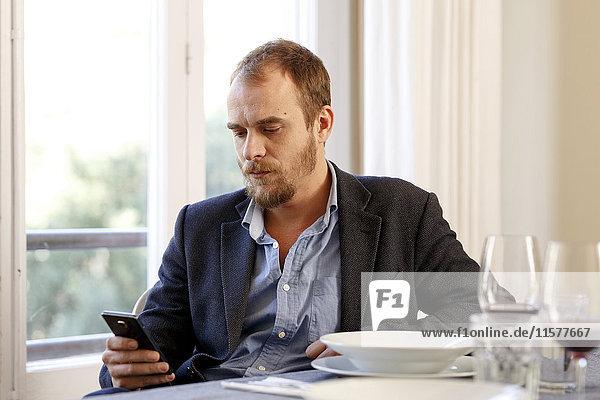 Mann am Esstisch sitzend  mit Smartphone