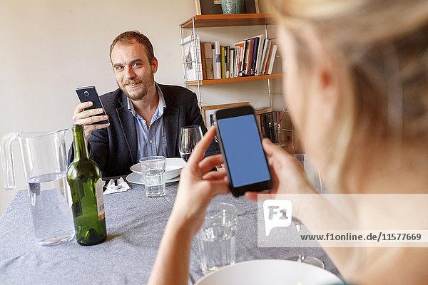 Mittelgroße erwachsene Paare zu Hause  die am Esstisch sitzen und Smartphones benutzen