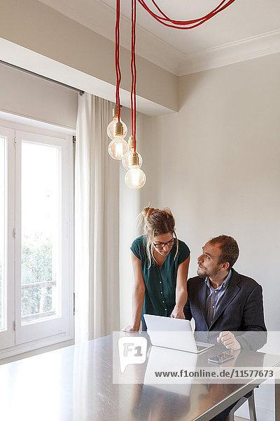 Mittelgroßes erwachsenes Paar zu Hause  Mann sitzt mit Laptop am Tisch  Frau zeigt auf den Bildschirm