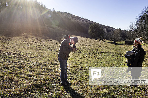 Man taking photograph of woman and baby boy  using medium format camera  in rural setting  Italy
