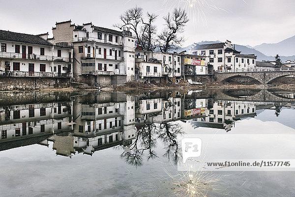 Spiegelbild von traditionellen Häusern und kahlen Bäumen am See  Lucun Village  Provinz Anhui  China