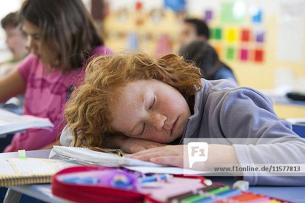 Primary schoolgirl asleep at desk in classroom