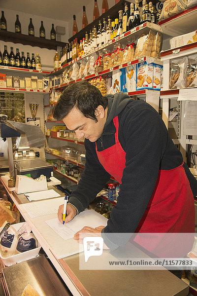 Reifer männlicher Lebensmittelhändler schreibt Notizen im örtlichen italienischen Lebensmittelgeschäft