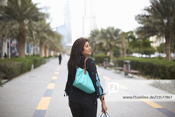 Rückansicht einer reifen Käuferin mit Einkaufstaschen  Dubai  Vereinigte Arabische Emirate