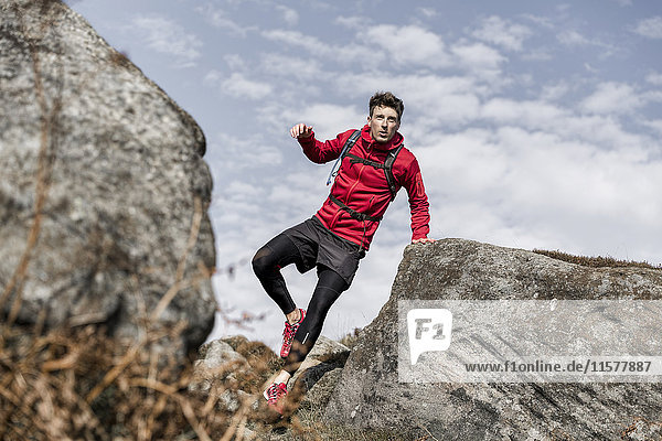 Männlicher Läufer läuft zwischen Felsblöcken am Stanage Edge  Peak District  Derbyshire  UK