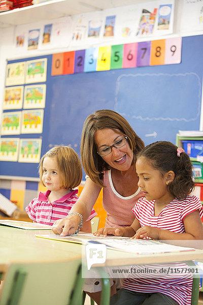Vorschulmädchen und Lehrer lesen Märchenbuch im Klassenzimmer