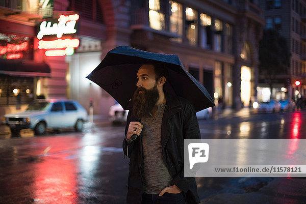Mittelgroßer erwachsener Mann  der nachts mit einem Regenschirm durch die Stadt läuft  Downtown  San Francisco  Kalifornien  USA Mittelgroßer erwachsener Mann, der nachts mit einem Regenschirm durch die Stadt läuft, Downtown, San Francisco, Kalifornien, USA