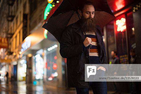 Mittelgroßer erwachsener Mann  der nachts mit einem Regenschirm durch die Stadt läuft  Downtown  San Francisco  Kalifornien  USA