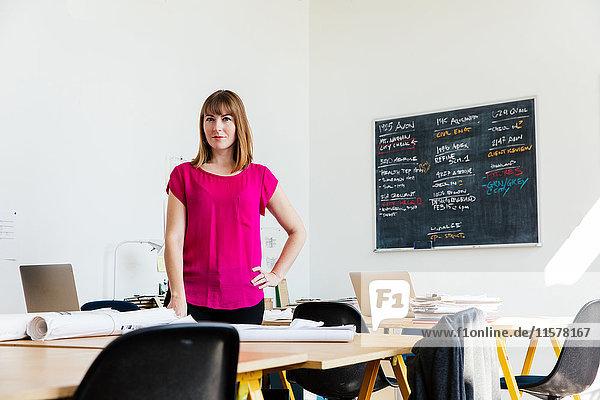 Porträt einer Frau im Büro  die in die Kamera schaut