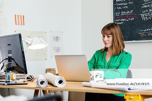 Frau sitzt im Büro am Schreibtisch und arbeitet am Laptop