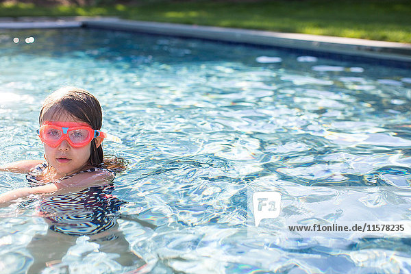 Porträt eines Mädchens mit rosa Schwimmbrille im Freibad