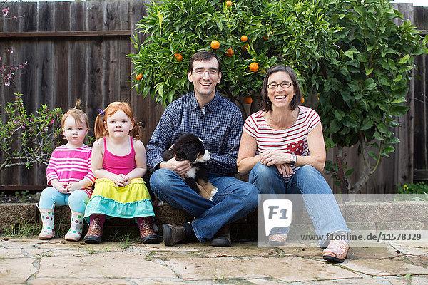 Porträt einer jungen Familie mit Hund  im Garten sitzend