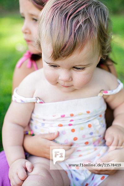 Close up of female toddler sitting on girl's knee in garden